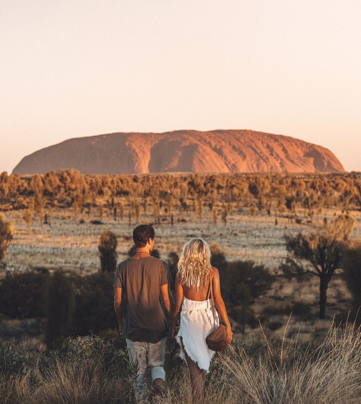 two people walking in the outback with Ayers Rock in the distance