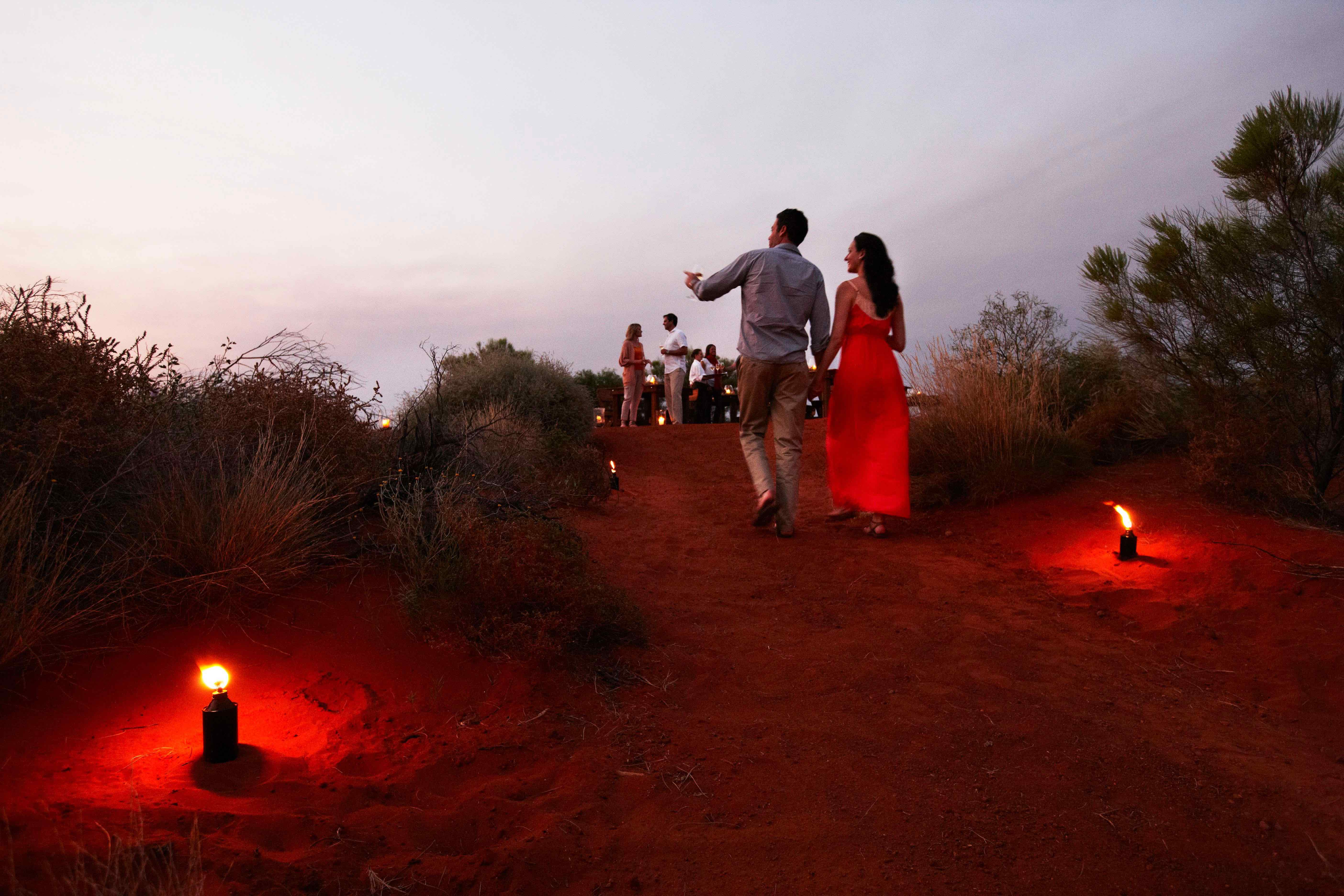 couple on red sand pathway at Ayers Rock resort