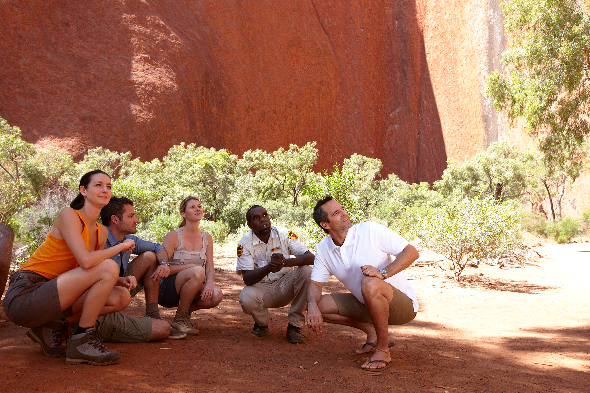people crouching in the shadow of Ayers Rock