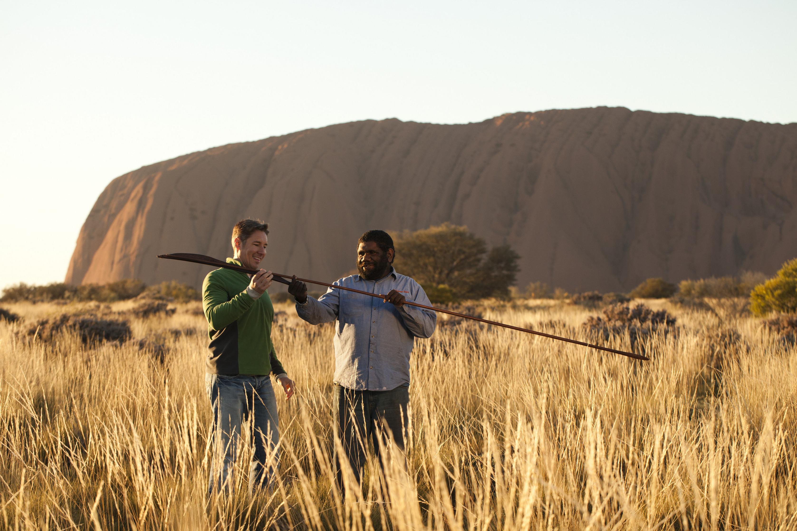 an indigenous man showing a tourist an atlatl