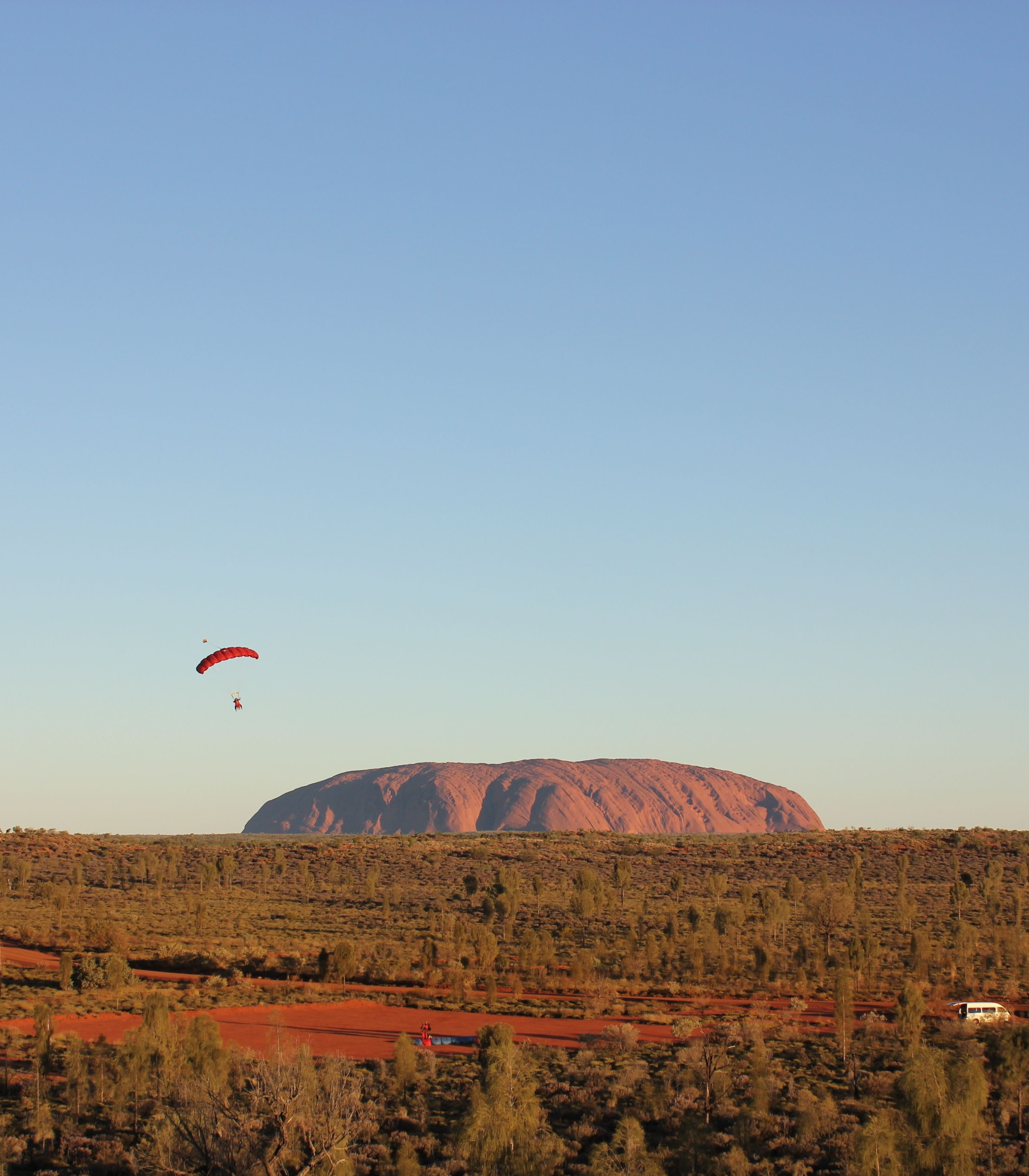 Parachute in the air front of Uluru