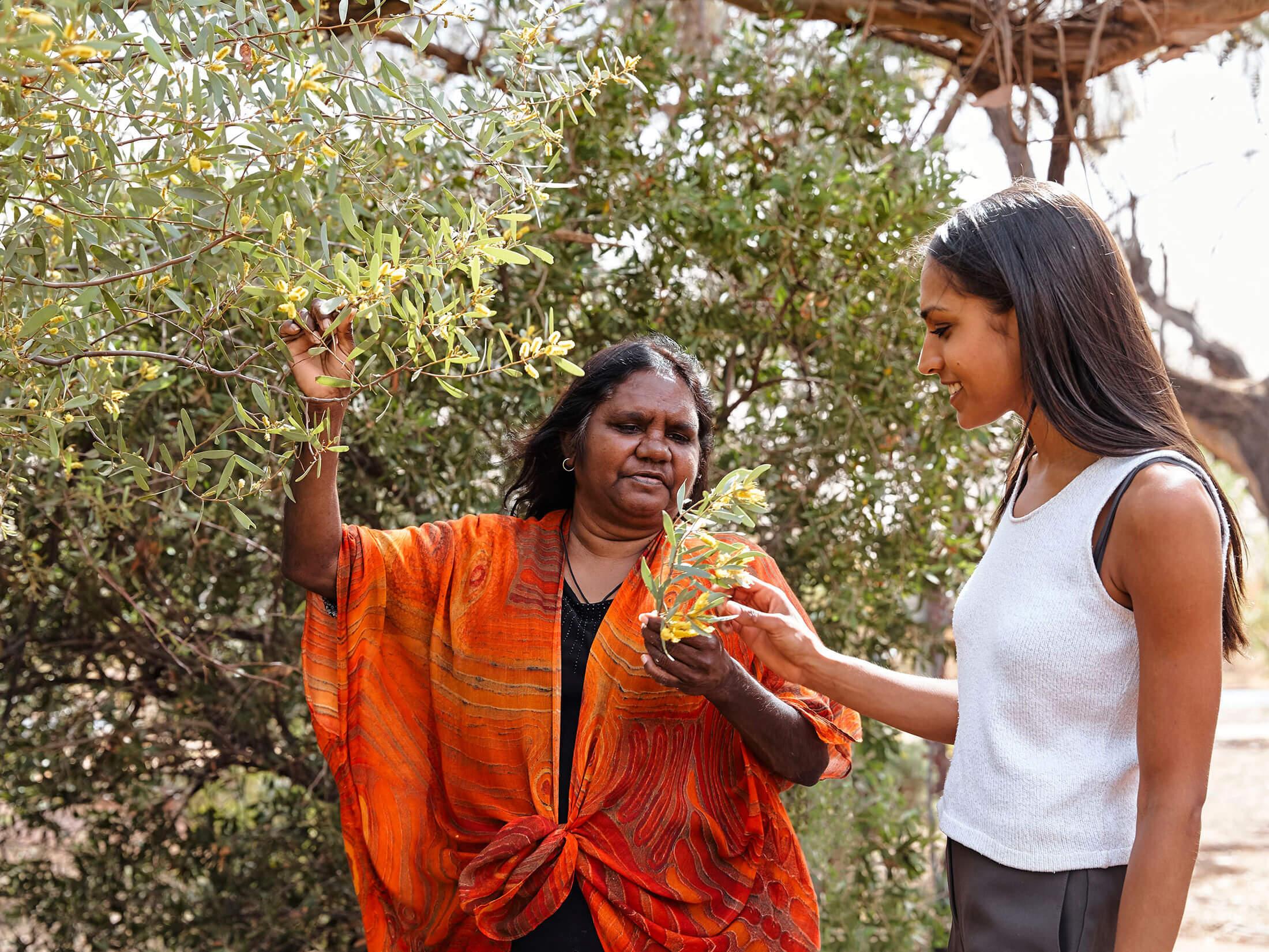 two women study a plant