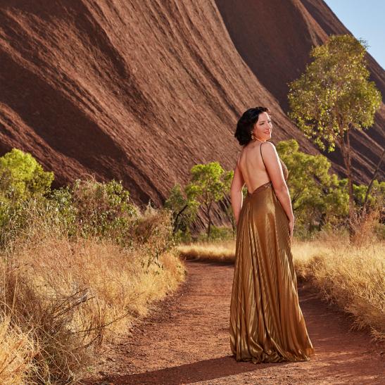 Woman in a dress beside Uluru