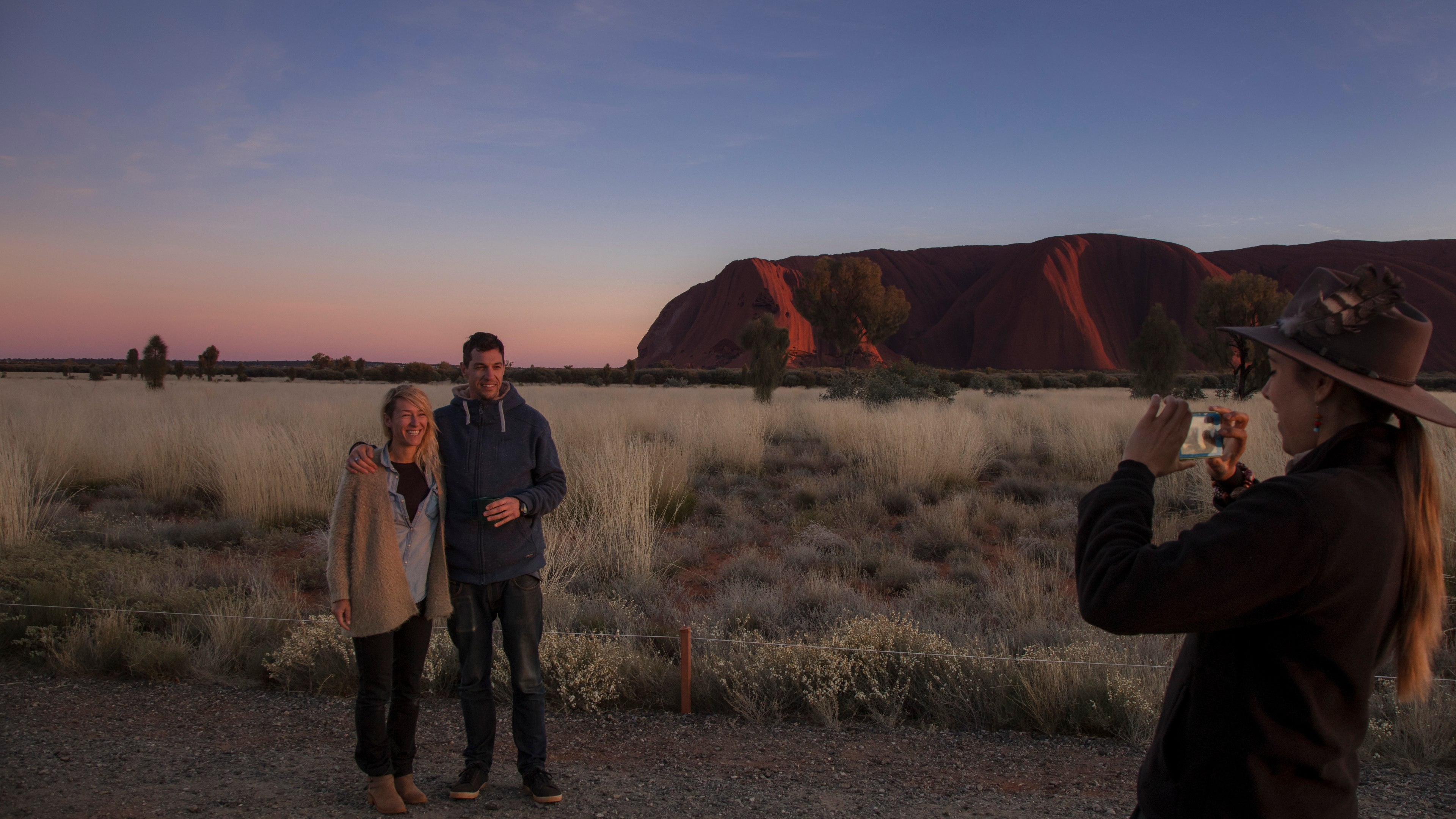 couple having their photo taken with a s unset and Ayers Rock in the background