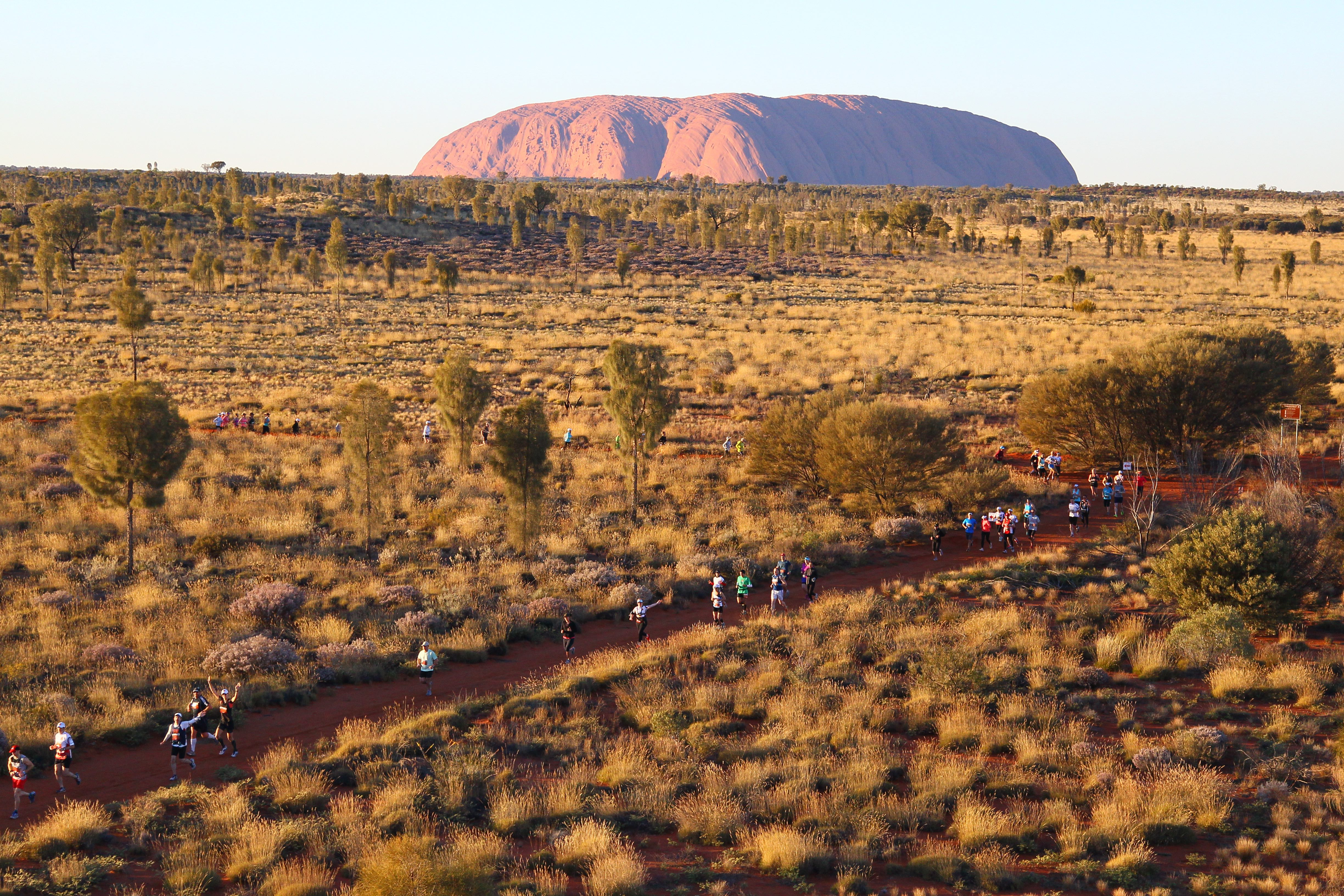 Runners compete in the Australian Outback Marathon with Uluru in the background