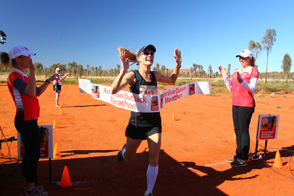 A woman crosses the finish line at the Australian Outback Marathon