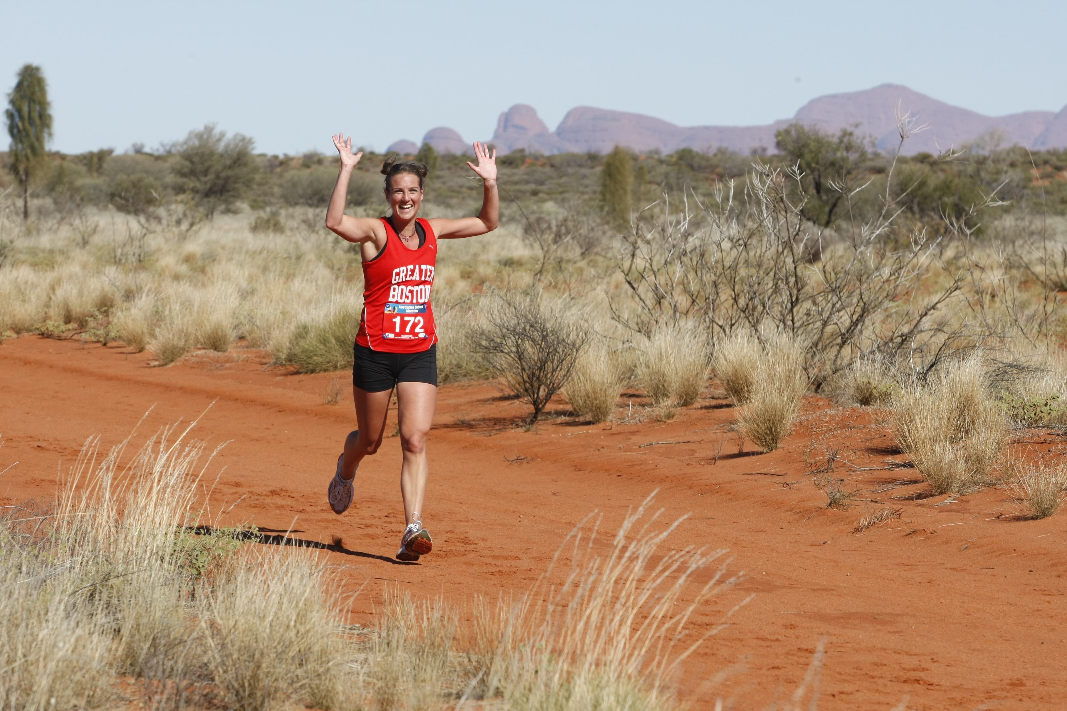 A Woman smiles while running in the Australia Outback Marathon