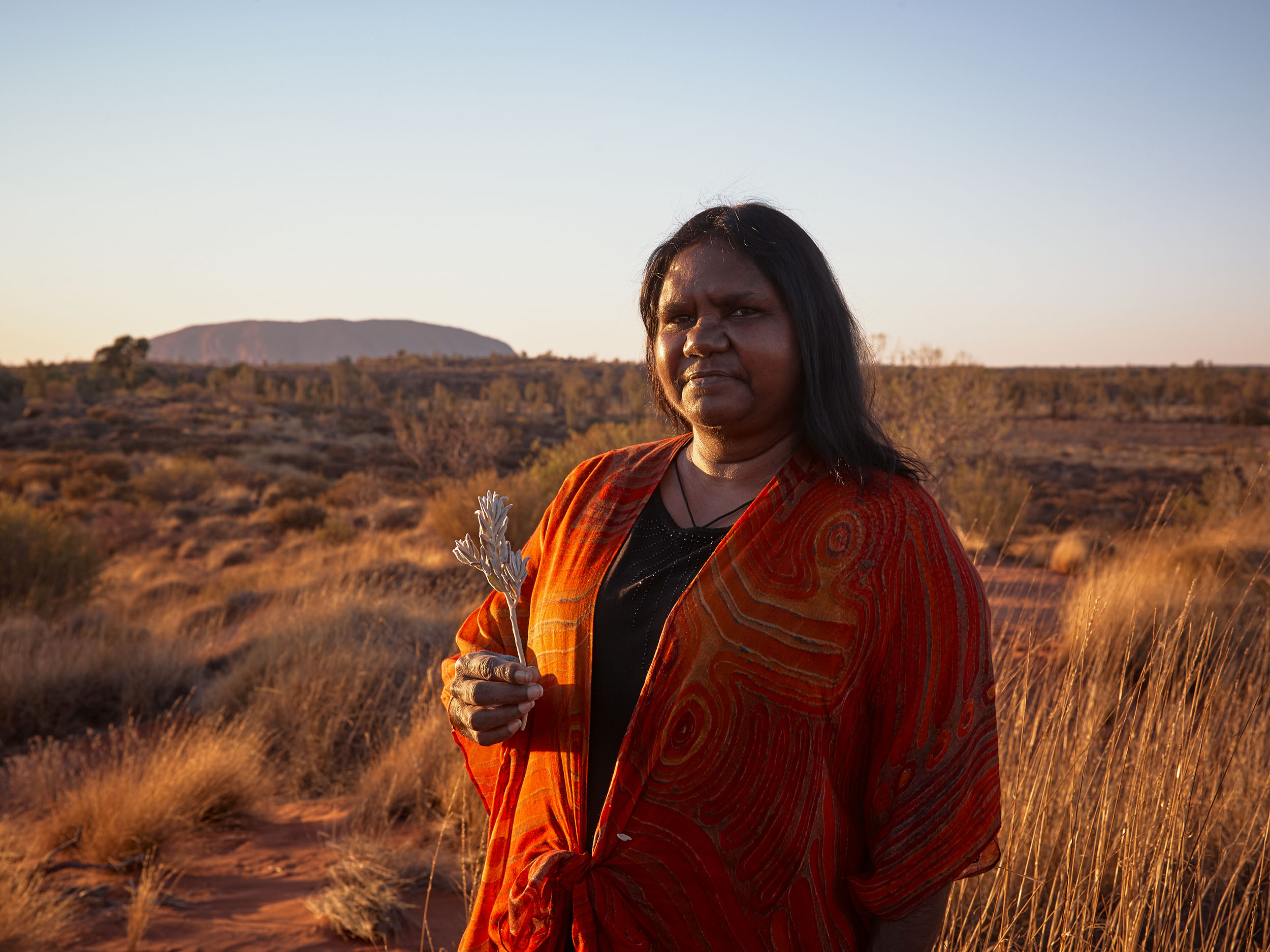 An Anangu woman holds a flower with Uluru in the background