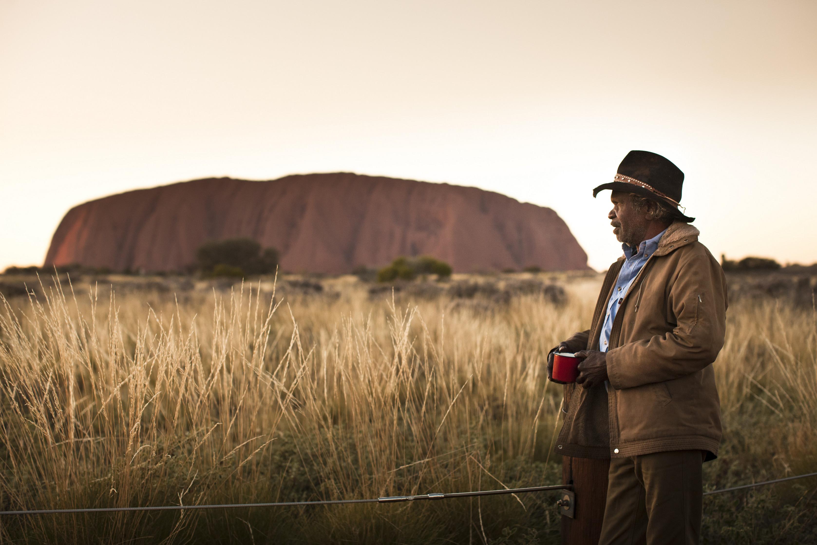 An Anangu man looks at Uluru