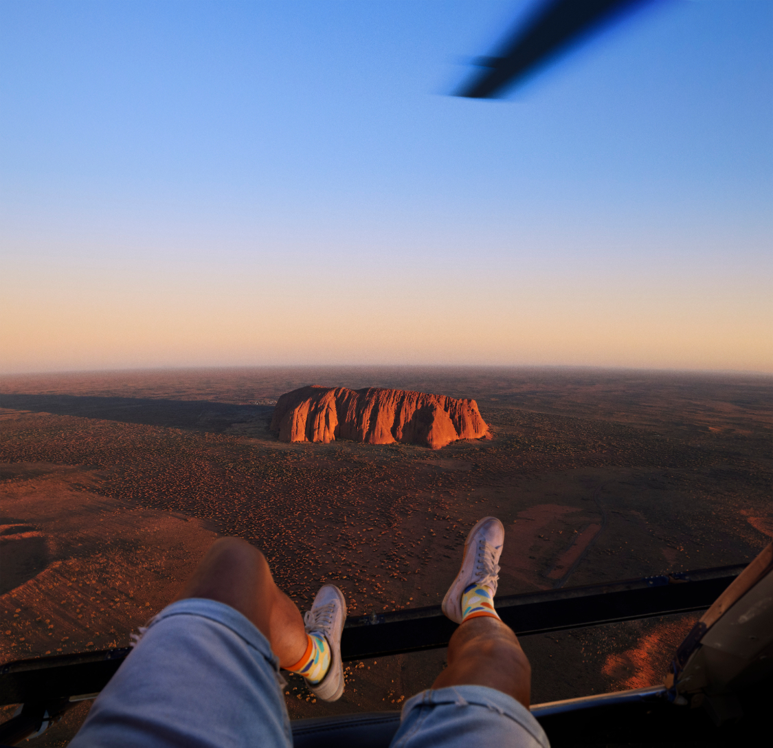 Man riding in a helicopter with his legs hanging out the side