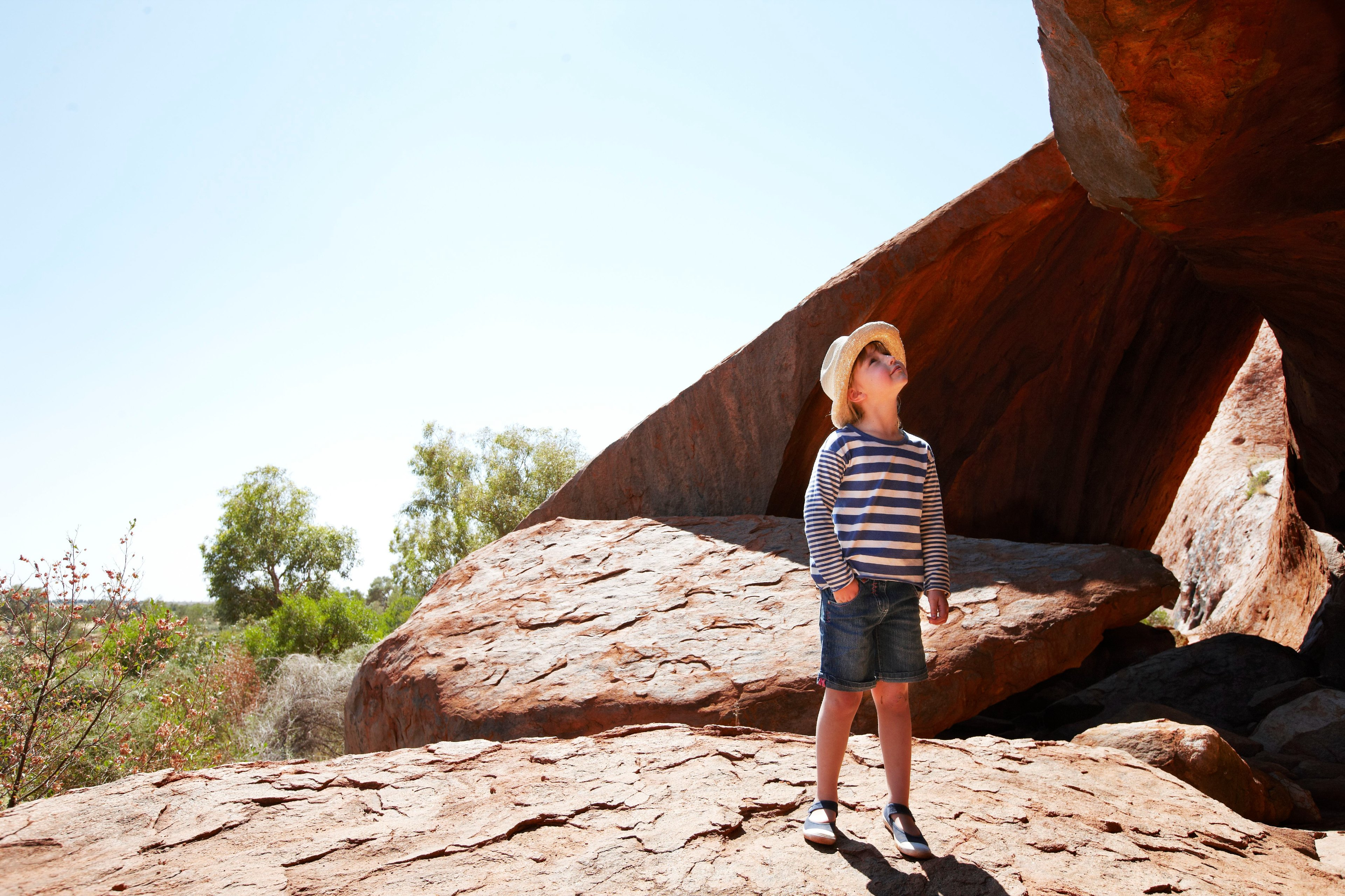 Young boy in hat and striped shirt looking at Ayers Rock