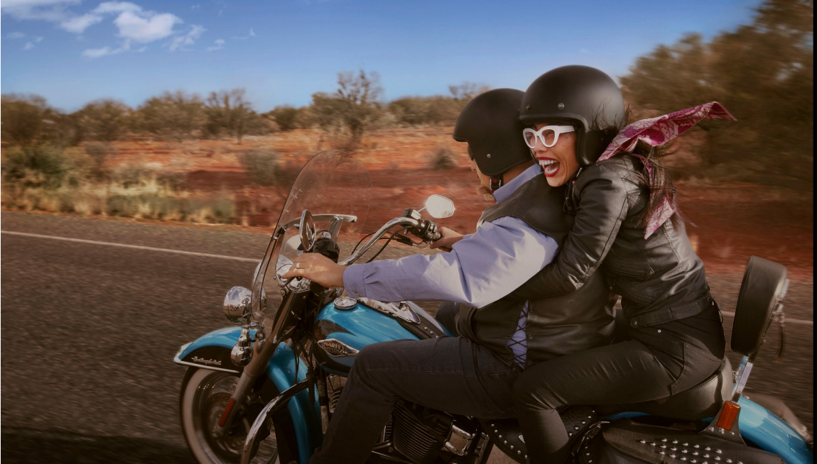 woman riding on the back of a Harley motorcycle