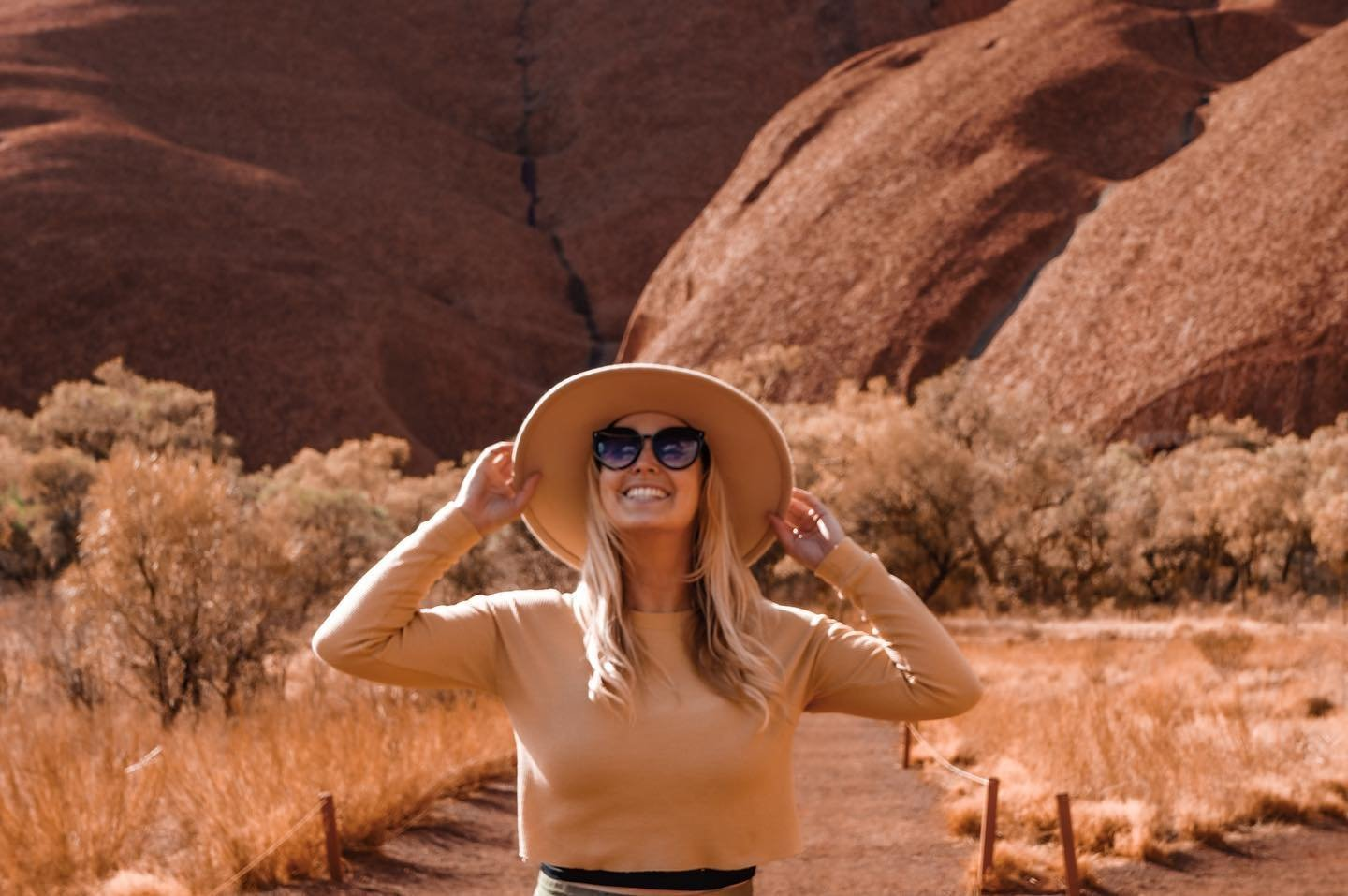 A woman holding her hat near Ayers Rock Resort