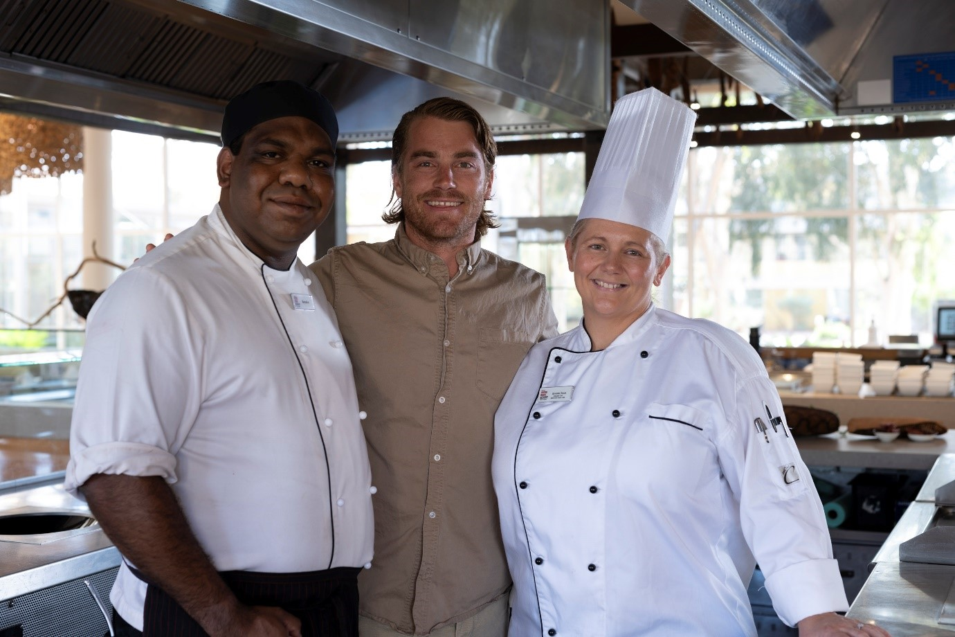 Three chefs (two male and one female) pose and smile in an industrial kitchen.