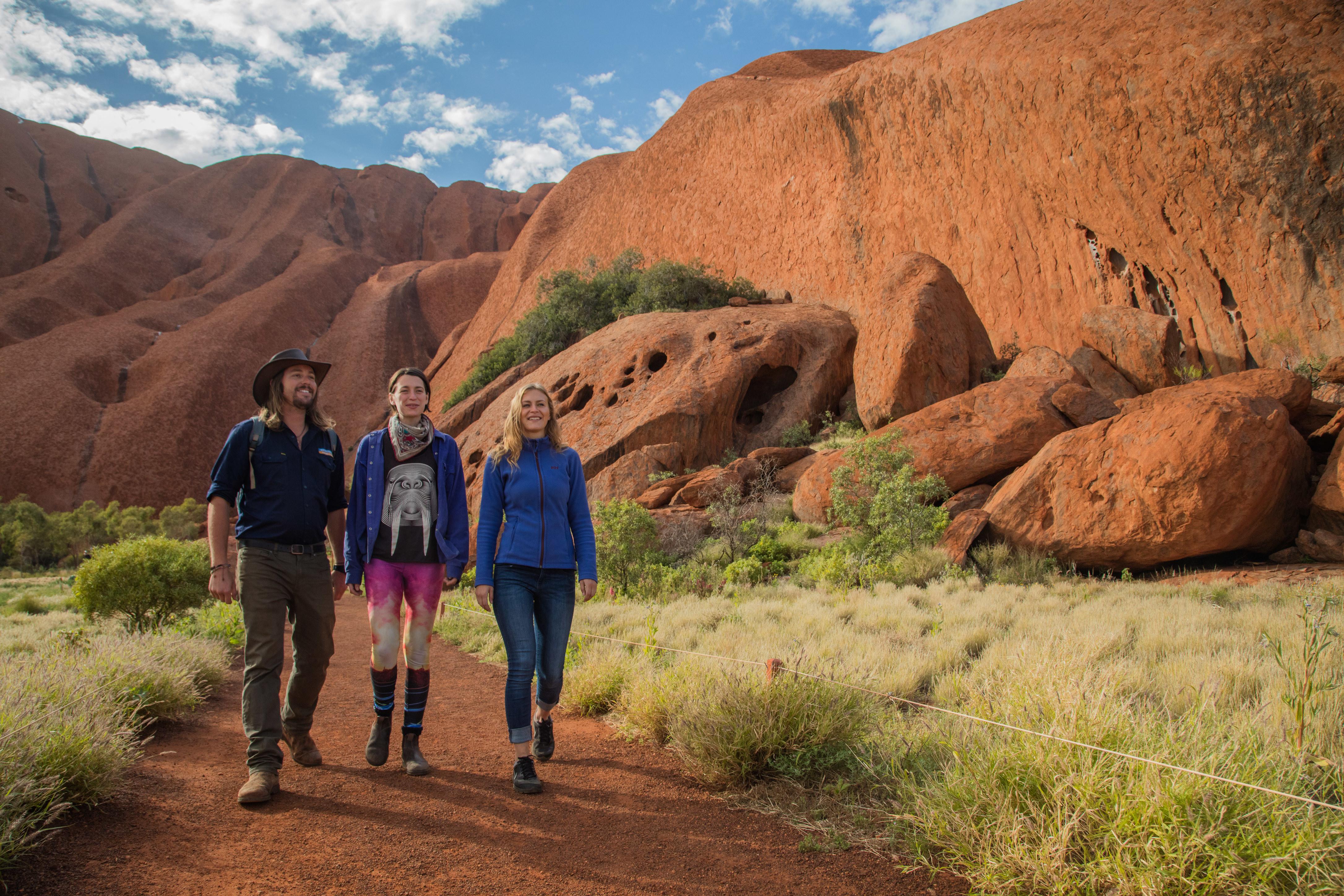 Three people hike on a sunny day near Uluru