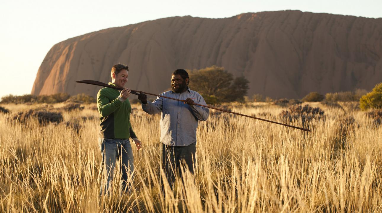A man and a guide looking at a spear