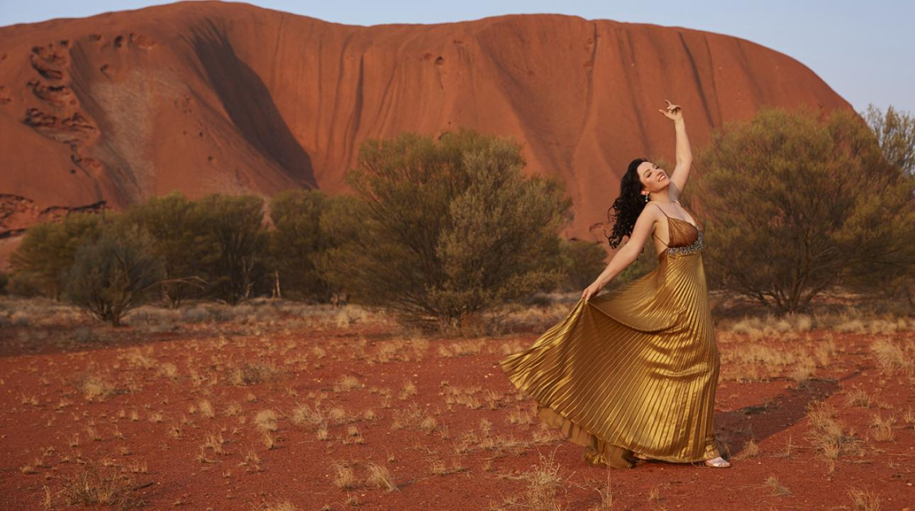 Woman dancing in a dress in front of Uluru