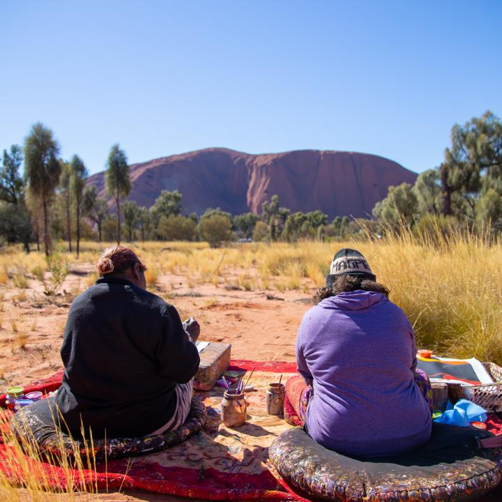 Two people sitting on blankets in front of Ayers Rock