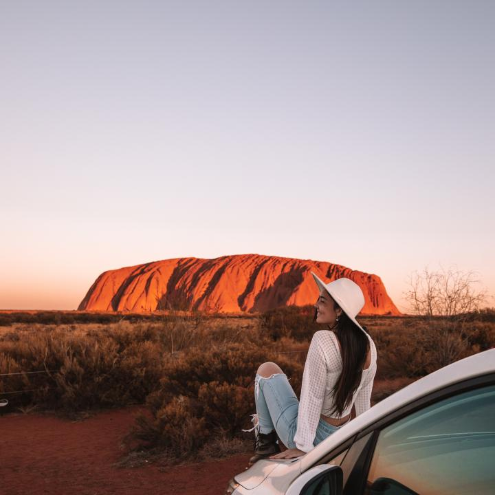 Woman sitting on car hood in front of Ayers Rock