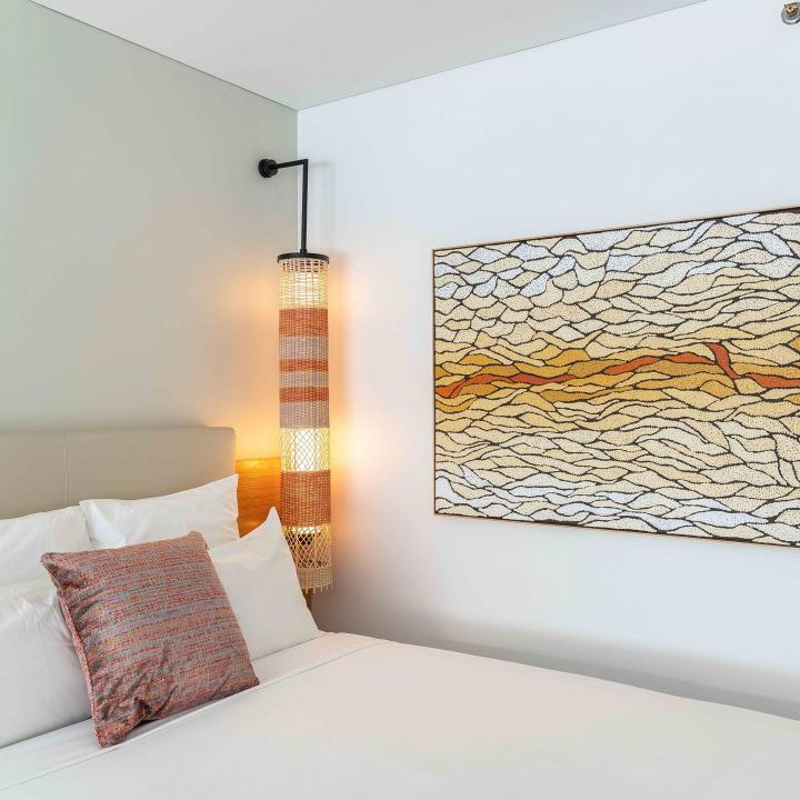 Hotel bed and large abstract painting