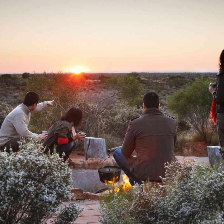 Group having coffee at sunrise at Ayers Rock outback