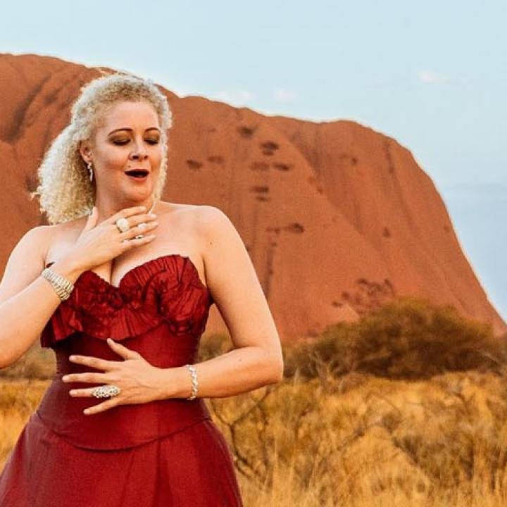 Opera singer in red gown in front of Uluru Ayers Rock
