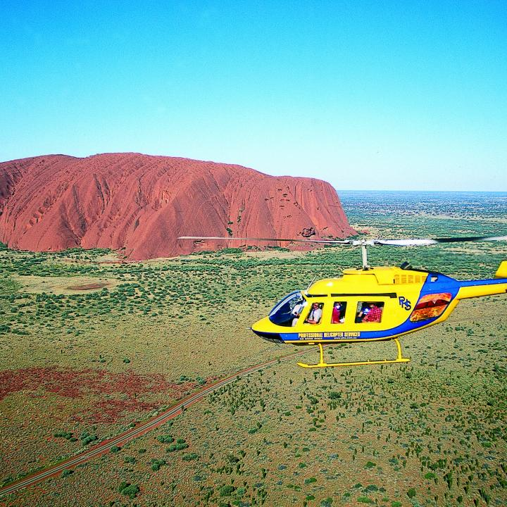 helicopter in flight by Ayers Rock