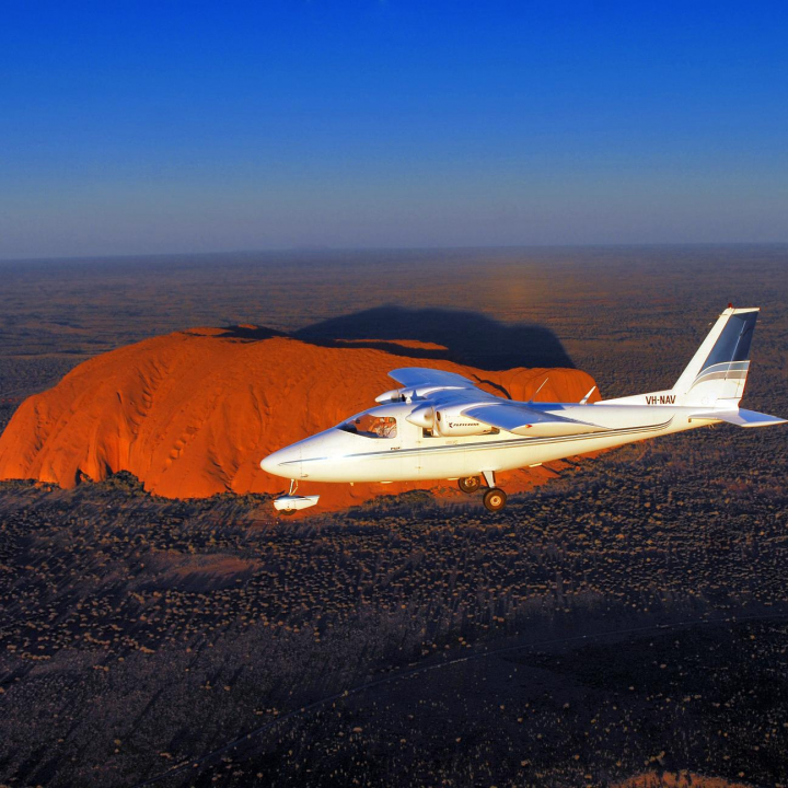 plane in the air over Ayers Rock