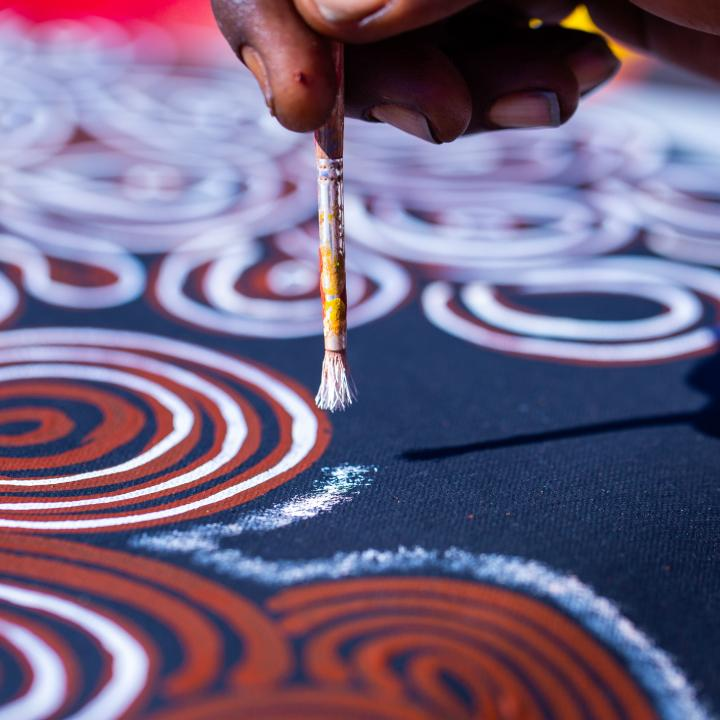 An individual creating indigenous artwork