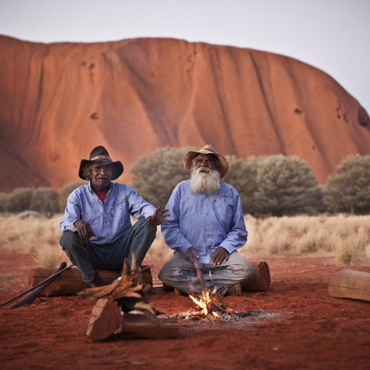 Two Anangu men sit by a fire