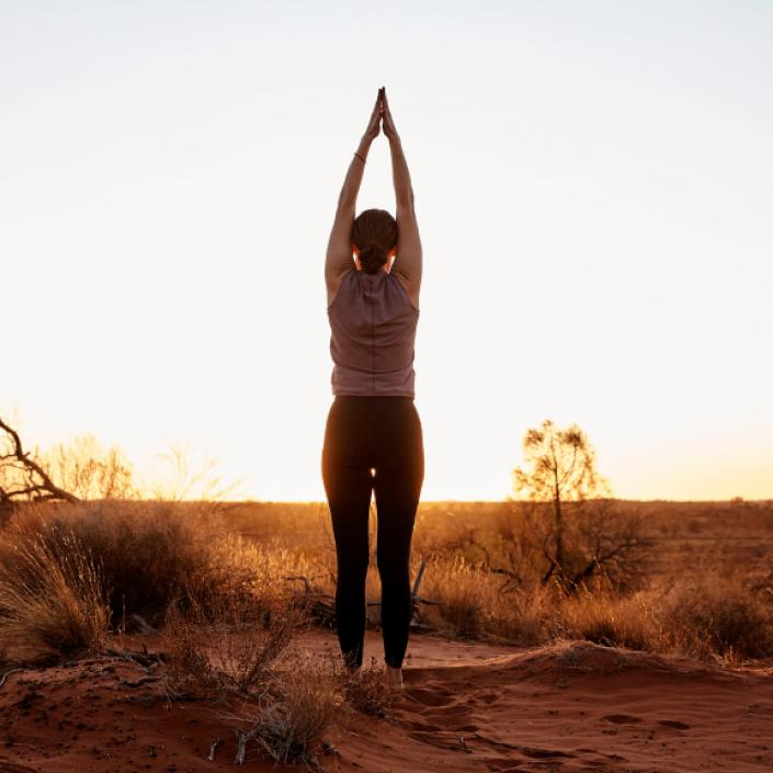 A woman performs yoga in the outback.