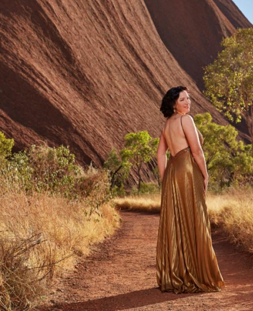 Woman in a dress beside Uluru