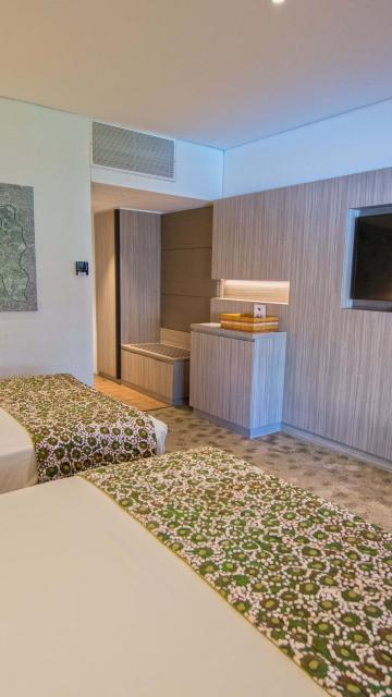 Two double beds in modern hotel room with tv on wall