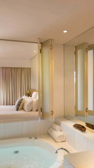 Large soaker tub adjoining luxurious hotel suite bedroom