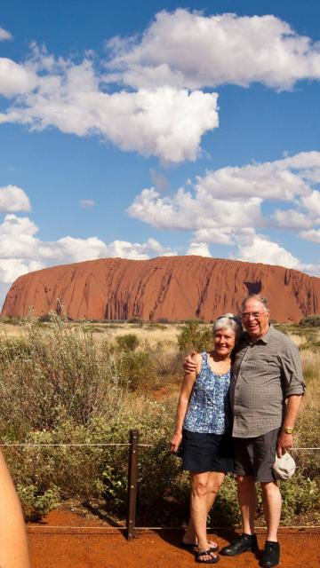 Tour guide taking a couples photo with Ayers Rock in the background