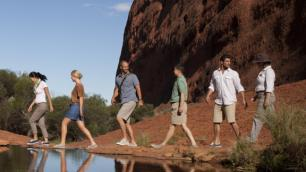 A group walks through the outback.