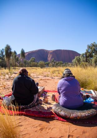 two people sitting on blankets in the outback